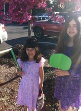 My daughters holding palm fronds made by the Primary children