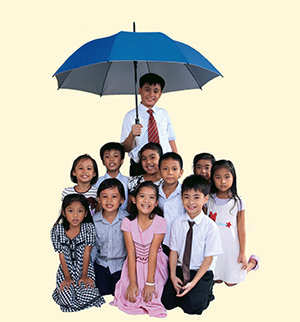 Children kneeling under an umbrella that one boy is holding. The umbrella decidedly does not cover the girls on the edge of the group.